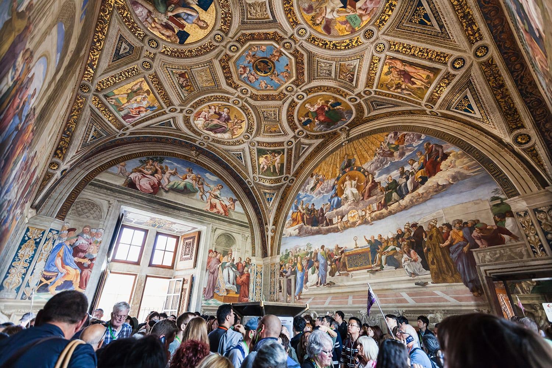 Visitors in Stanza della segnatura (Room of the Signatura) decorated by Raphael's frescoes in Raphael Rooms (Stanze di Raffaello) of Vatican museums, Rome, Italy
