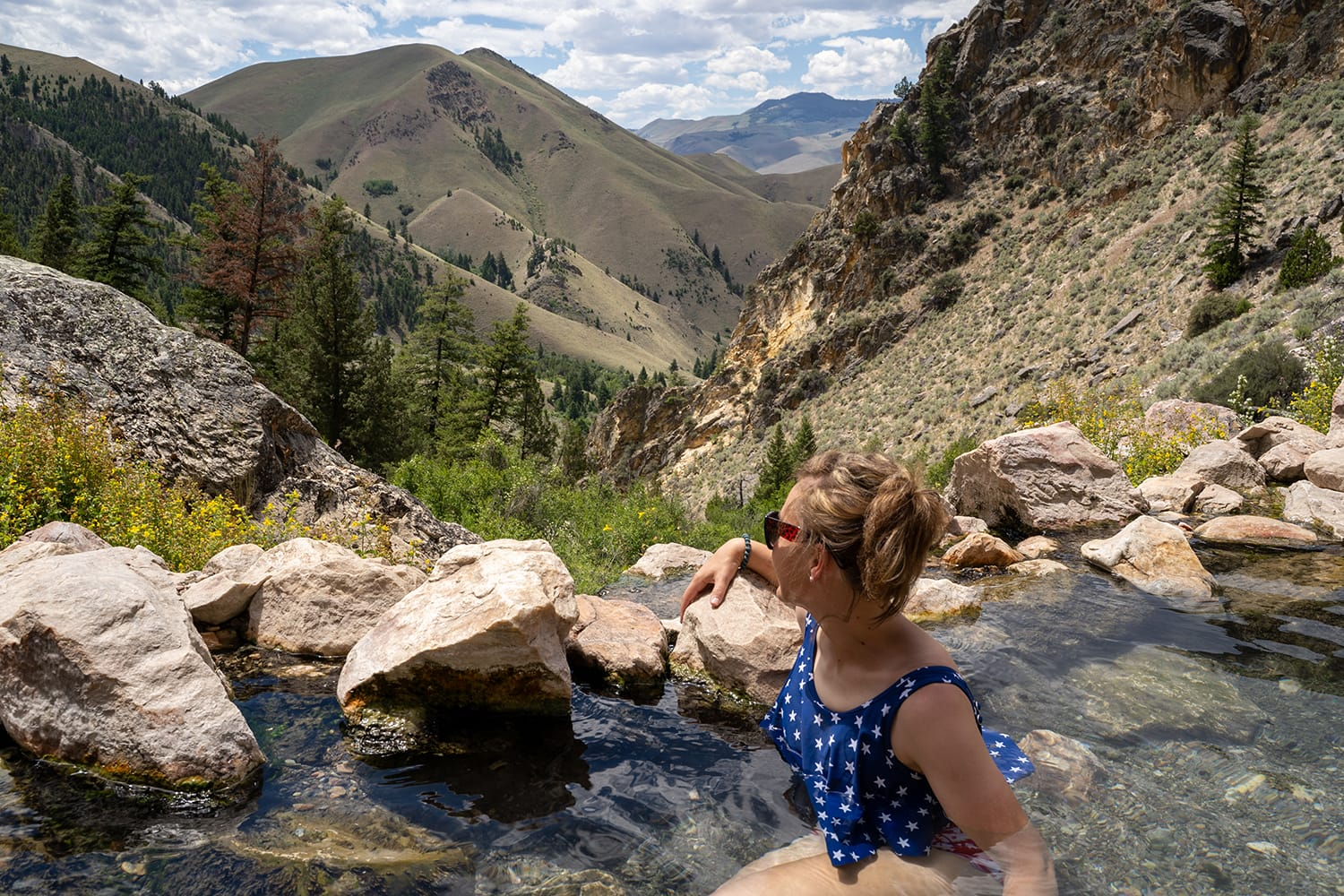 Cute adult woman wearing an American flag swimsut soaks and enjoys the Goldbug Hot Springs in the Salmon Challis National Forest of Idaho
