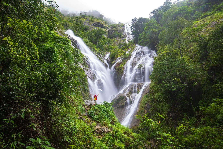 Young girl hiking on Pi-tu-gro waterfall, Beautiful waterfall in Tak province, Thailand.