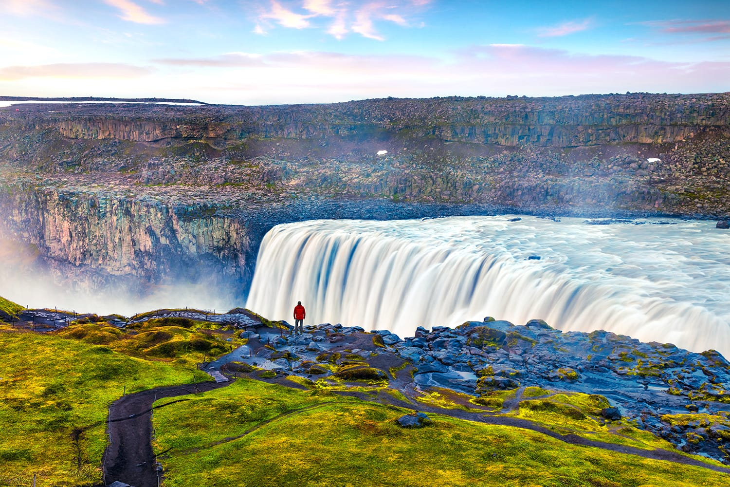 Tourist admiring view of falling water of the most powerful waterfall in Europe - Dettifoss. Colorful summer sunrise in Jokulsargljufur National Park, Iceland.