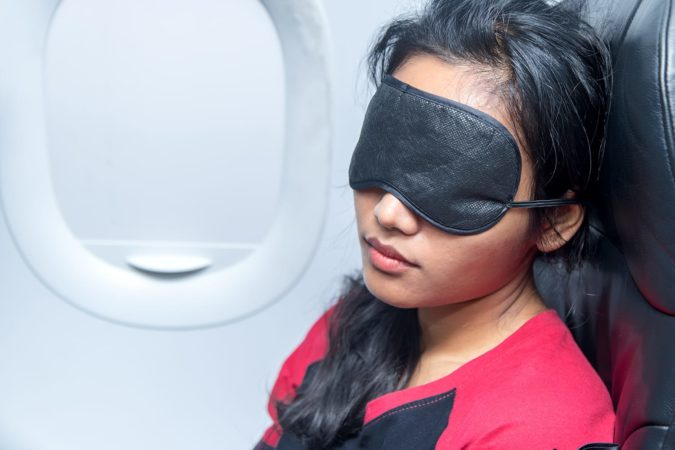 Portrait of a woman sleeping in an airplane. Young woman sleeping with a sleep mask on the eyes in a flying aircraft. Girl sleeps in the airplane in a vertical position on seat covered with eye flap.