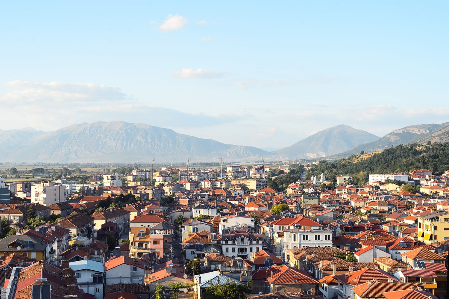 Panoramic aerial view to Korca, the town in southwest of Albania, the mountains and the red tile roofs of its buildings.