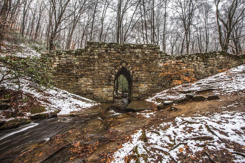 Snowy Historic Poinsett Bridge made of stone and Stream near Greenville South Carolina SC.