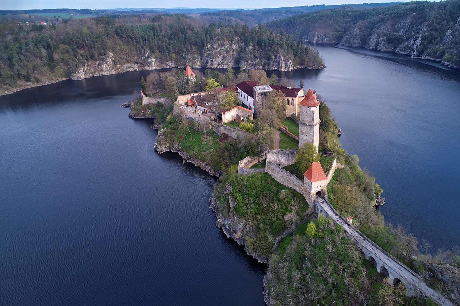 Aerial view on czech medieval secular castle Zvikov, situated on rocky outcrop above the confluence of two rivers in the centre of beautiful, spring nature.